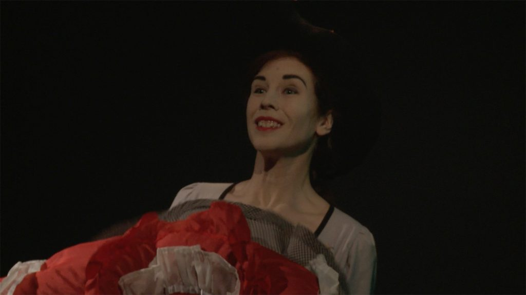 Video still from artwork where artist Maria Norrman interprets and invokes dance artist Jane Avril. The artist in a dancing pose, dressed in cancan clothing.