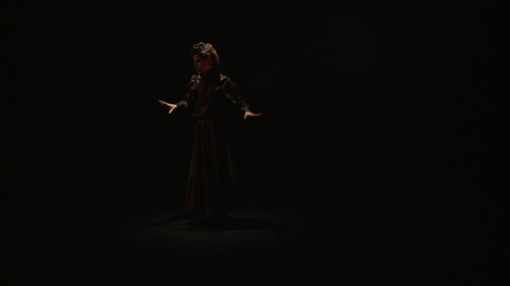 Video still from artwork where artist Maria Norrman interprets and invokes dance artist Jane Avril. The artist in a dancing pose, dressed in black 19th century clothing.
