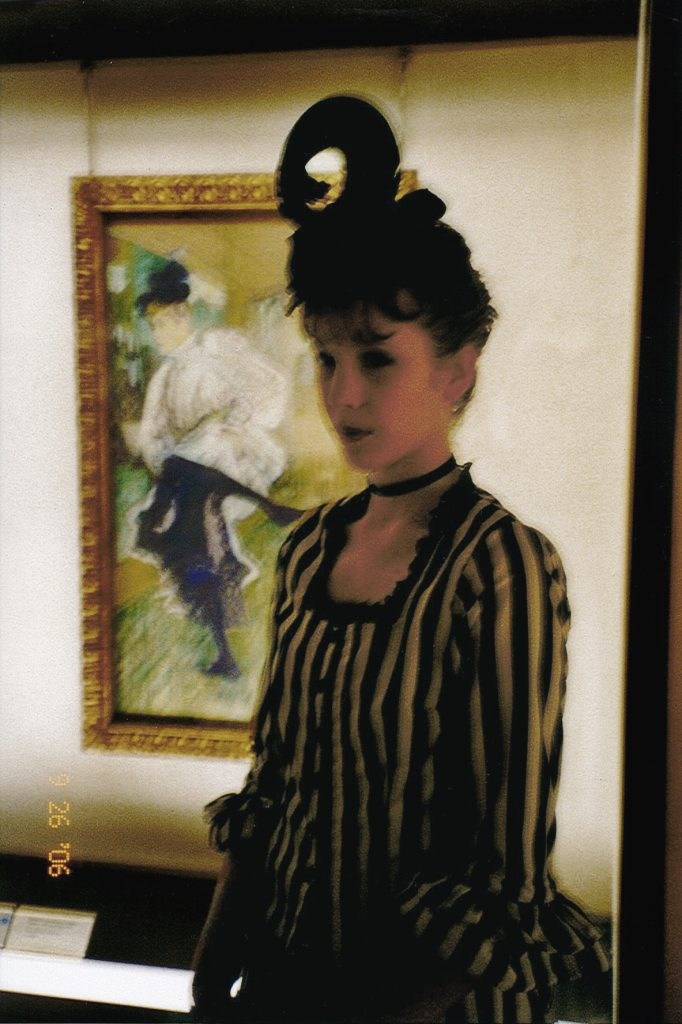 Photo of the artist Maria Norrman dressed as dance artist Jane Avril, standing in front of a Toulouse Lautrec painting of her.