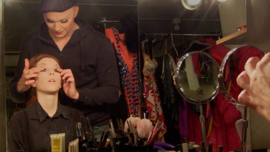 Video still from Millennium Star, where a drag artist makes artist Maria Norrman into a drag queen. Two persons in half drag, one adjusts the eyelashes of the other.