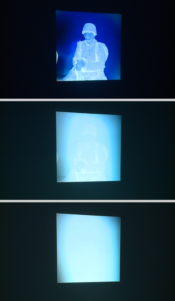 The video projection Blue Prints. Images of an inverted analogue negative of a seated man in a uniform, which fades from visible to white.