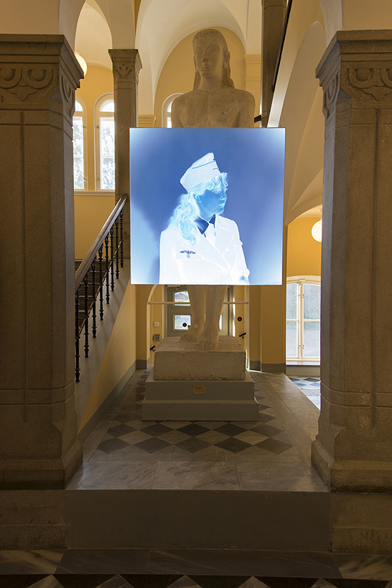 The video projection Blue Prints installed and projected on a frame in front of a classical sculpture.  An image of an inverted analogue negative of a girl in uniform.