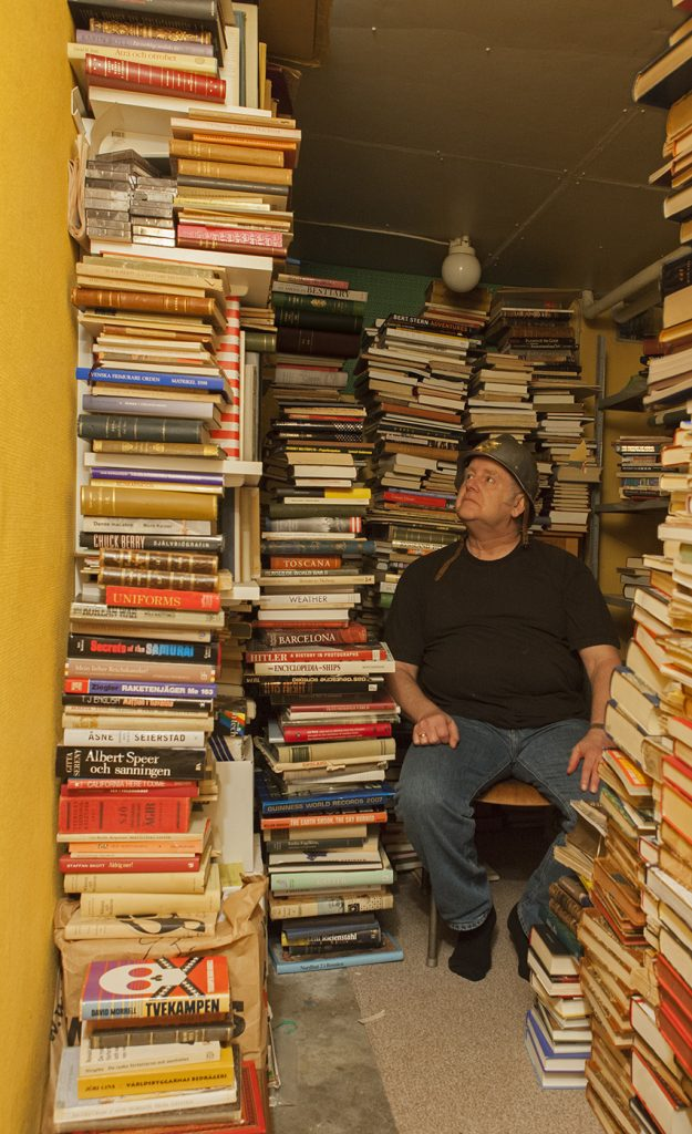 The photo work Burden of Knowledge.  A seated man with a helmet sits in a room with crammed bookshelves and book piles, from top to bottom.
