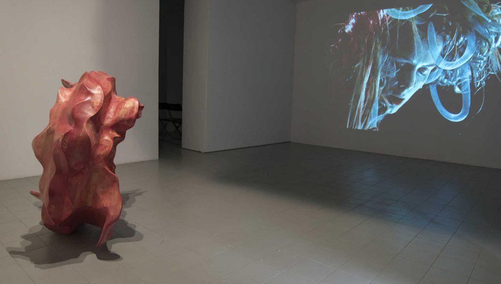 Pink wood sculpture on the floor, Saghi - Samaneh Reyhani Blue wall projection,Head On My Dear - Helene Nymann