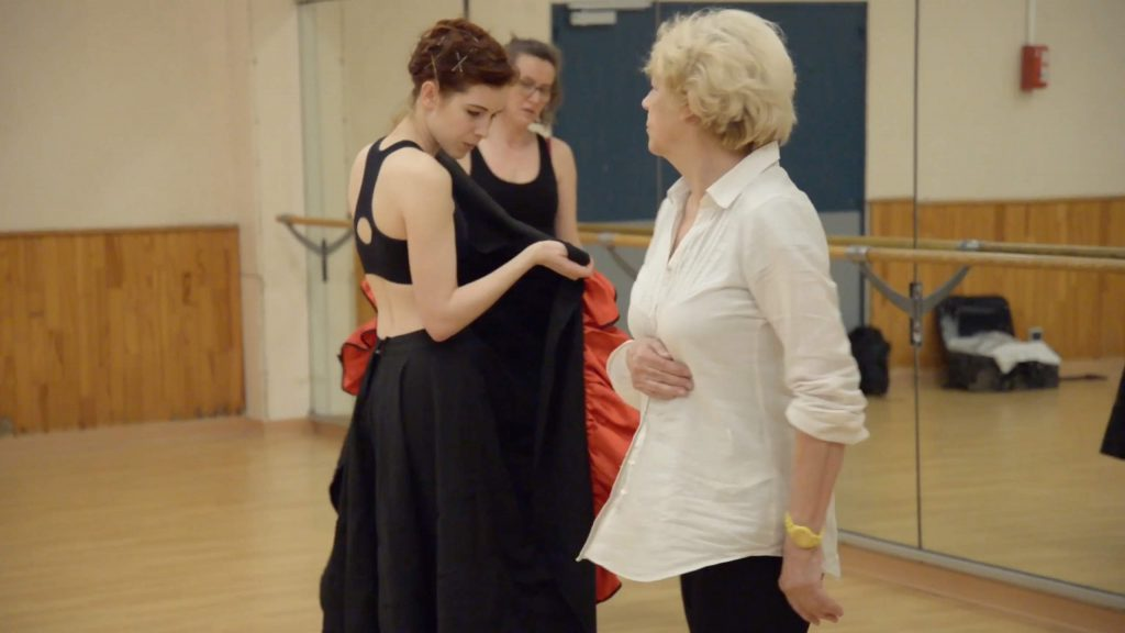 Video still from artwork where artist Maria Norrman partakes in a cancan dance class. She is taught by a teacher, along with two other participants.